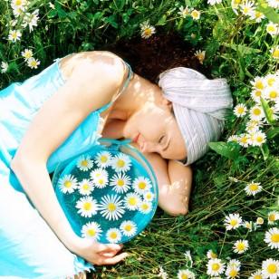Una mujer, tumbada con una cesta de flores de manzanilla