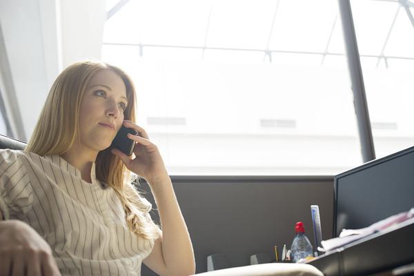 Una mujer, hablando por el teléfono móvil en la oficina