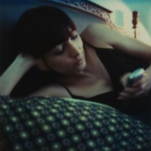 Una chica consulta el móvil en la cama