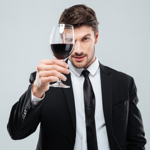Focused young male sommelier in suite looking at red wine in glass over white background