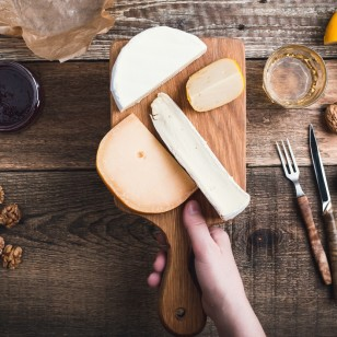 Close up hand holding cutting board  with cheese, snack food on rustic table viewed from above