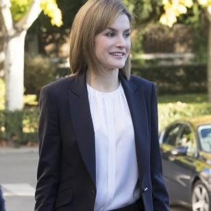 Doña Letizia con su traje azul marino de Hugo Boss, que combina con una camisa blanca con jareta central y cuello origami de Carolina Herrera.