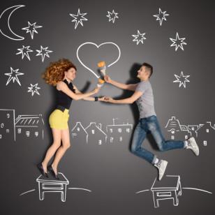 Una pareja se mira junto a un corazón de tiza dibujado en la pared