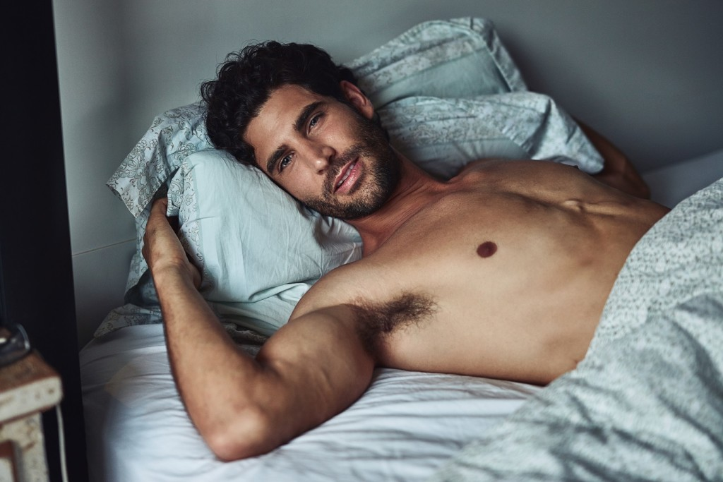 Cropped shot of a handsome young shirtless man lying in bed at home