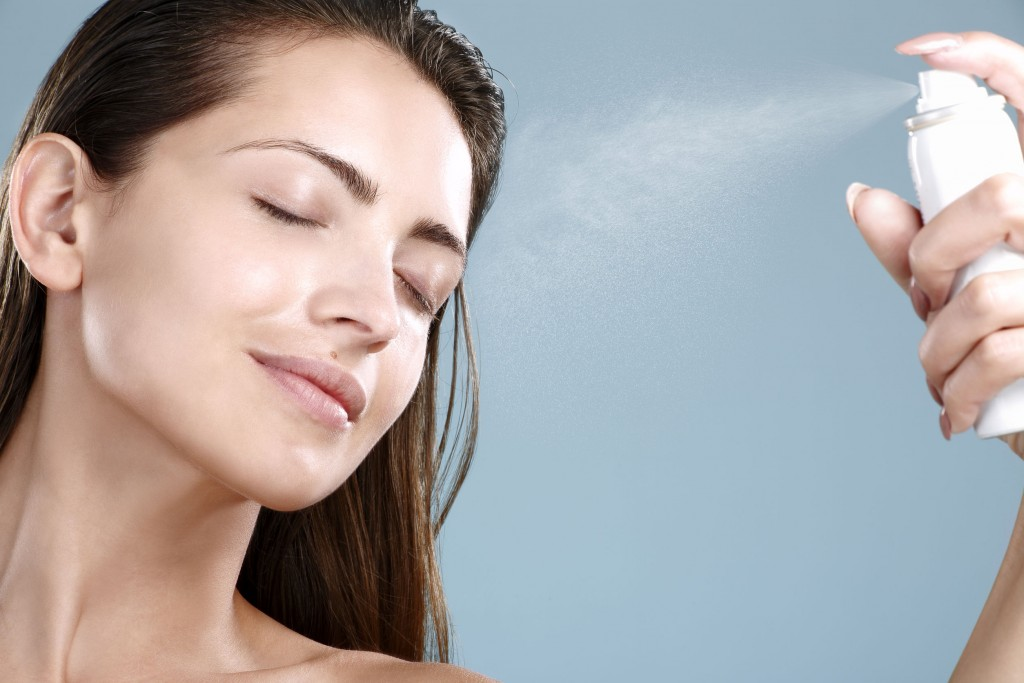 26170435 - beautiful woman applying spray  water treatment on face on blue wall