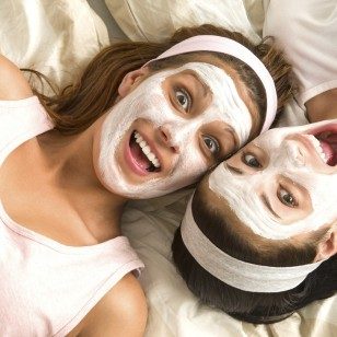 Serene girls lying on bed wearing cosmetic mask and laughing