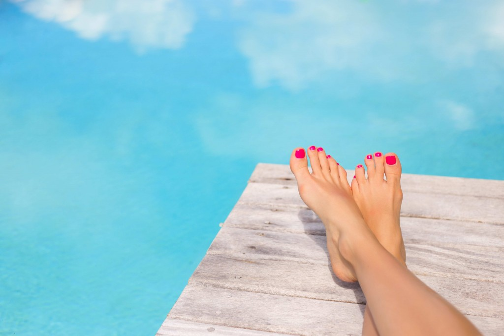 Bare woman feet on wooden deck by the swimming pool