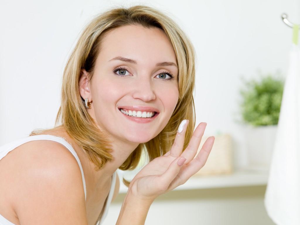 Beautiful happy girl applying moisturizer  cream on face standing in the bathroom